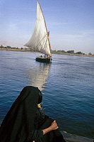 0129924 © Granger - Historical Picture ArchiveEGYPT: FELUCCA ON THE NILE.   A felucca sailing on the Nile River in Egypt, as a woman watches from shore. Photographed c1974.
