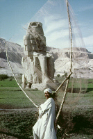 0354755 © Granger - Historical Picture ArchiveEGYPT: COLOSSI OF MEMNON.   A Nile fisherman standing before one of the 65-foot statues of the Pharaoh Amenhotep III, known as the Colossi of Memnon, at Thebes, Egypt. Photograph, c1970.
