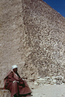 0354824 © Granger - Historical Picture ArchiveEGYPT: CHEOPS PYRAMID.   An Arab guide seated at the base of the Great Pyramid of Cheops at Giza, Egypt. Photograph, c1970.