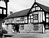 0001328 © Granger - Historical Picture ArchiveENGLAND: RED LION INN.   The Red Lion Inn, Weobley, Herefordshire, England. An example of English Tudor half-timbering. Photograph, mid-20th century.