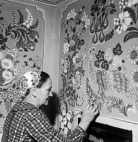 0165920 © Granger - Historical Picture ArchiveHUNGARY: WALL PAINTING.   A woman in Kalocsa, Hungary, wearing a headdress with an embroidered floral design as she decorates a wall with a similar floral and peacock design. Photographed c1970.