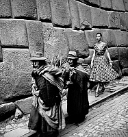 0118631 © Granger - Historical Picture ArchivePERU: FASHION MODEL, 1950s.   A fashion model following indigenous women on a street in Peru. Photographed by Toni Frissell, 1950s.