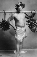 0351650 © Granger - Historical Picture ArchiveTAHITIAN MAN, c1920.   Portrait of an unidentified Tahitian man carrying bunches of Fei bananas. Photograph, c1920.