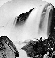 0117786 © Granger - Historical Picture ArchiveNIAGARA FALLS.   A man standing by a bridge at the Cave of the Winds, at the lower part of Niagara Falls, New York. Photographed by Charles Bierstadt, late 19th century.