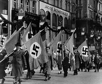 0621380 © Granger - Historical Picture ArchiveVIENNA: SWASTIKA, 1938.   Men with Nazi flags on parade during May Day celebrations in Vienna, Austria. Photograph, 1 May 1938.