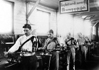 0623554 © Granger - Historical Picture ArchiveDISABLED VETERANS, 1917.   Four soldiers, each with a prosthetic arm, working in a machine shop at the Institute de Port Villez, Belgium. Photograph, 1917.