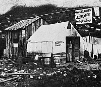 0112987 © Granger - Historical Picture ArchiveDAWSON CITY, c1900.   A laundress and fortune teller in the doorway of her shop in the gold mining town of Dawson City, Yukon Territory, Canada. Photograph, c1900.