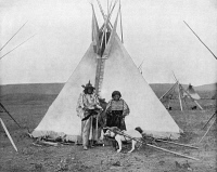 0353240 © Granger - Historical Picture ArchiveCANADA: TSUU T'INA.   Bull's Head, a Tsuu T'ina chief, and his wife in front of their tipi in Canada, possibly Alberta. Photograph, c1890.