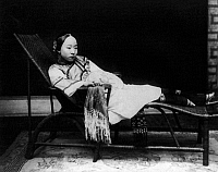 0115746 © Granger - Historical Picture ArchiveCHINA: WOMAN.   Chinese woman with bound feet reclining on a chaise lounge in China. Photograph, late 19th or early 20th century.
