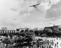 0623551 © Granger - Historical Picture ArchiveGUATEMALA: LEAFLET DROP.   A small plane drops leaflets to Guatemalans listening to a speech by Colonel Carlos Castillo Armas in the square in Guatemala City, Guatemala. Photograph, 1954.