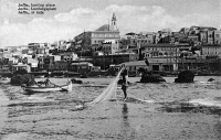 0623443 © Granger - Historical Picture ArchiveJAFFA: HARBOR, c1921.   Fisherman draws in a net in the waters of Jaffa harbor; buildings rise behind. Photograph, c1921.
