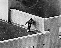 0093402 © Granger - Historical Picture ArchiveBOGSIDE RIOT, 1970s.   A man on a Londonderry roof prepares to throw a homemade bomb during a riot, 1970s.