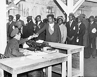 0594477 © Granger - Historical Picture ArchiveUNITED STATES OF AMERICA.   Unemployed African-American men from New York who are assigned to a reforestation project, receive their identity cards from non-commissioned officer C. E. Manley. The unemployed men were assigned to a reforestation project that was organized within the framework of 'Emergency Conservation Work' also know as the 'Civilian Conserva
