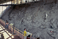 0167497 © Granger - Historical Picture ArchiveUTAH: DINOSAUR QUARRY.   Visitors viewing the cliff face, containing hundreds of fossilized dinosaur bones, inside the Dinosaur Quarry at Dinosaur National Monument, northeastern Utah. Photographed c1975.