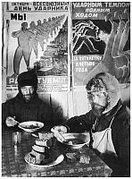 0038050 © Granger - Historical Picture ArchiveRUSSIA: BRICKLAYERS, 1932.   Two bricklayers dining in a communal kitchen, under Soviet posters urging increased worker productivity during the first five-year plan. Photographed by Margaret Bourke-White, 1932.