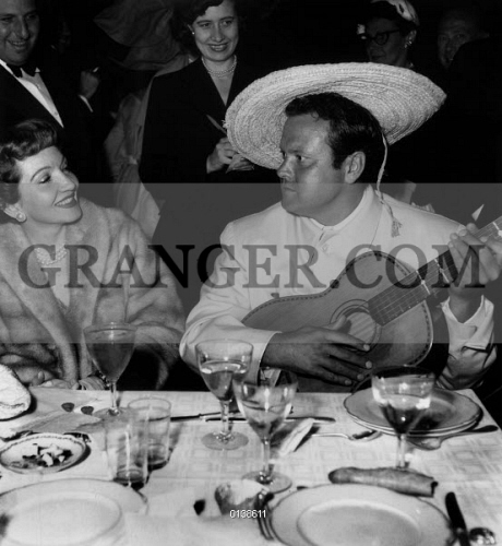 4ec86e149289 CLAUDETTE COLBERT AND ORSON WELLES. Claudette Colbert eand Orson Welles at  Jacques Fath's party in
