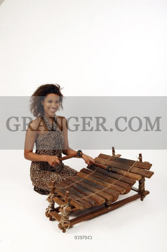 Image of MUSICIAN AND INSTRUMENT  - Young African Woman Playing An